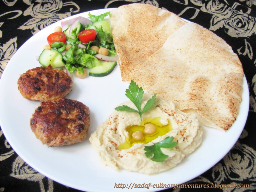 Hummus with kabobs kebabs , pita and salad