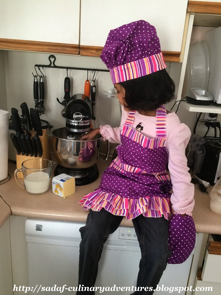 Little girl baking in the kitchen with chef hat and apron